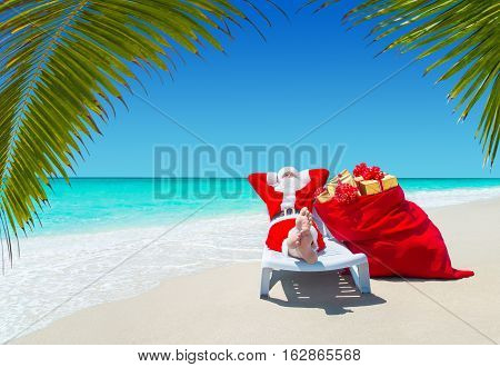 Santa Claus with Christmas sack full of gifts relax on sunlounger barefooted at perfect sandy ocean beach under palm tree leaves. Happy New Year travel destinations for tropical vacations concept.