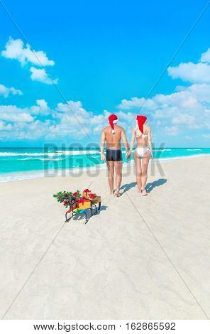 Young lovers couple walking back at sea beach in red santa hats with sleds gifts and decorated Christmas tree. Happy New Year travel destinations for tropical vacations concept.