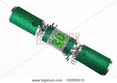 A shot of a 30th Birthday or Anniversary Cracker also known as a Bon Bon. A cracker consists of a cardboard tube wrapped in a brightly decorated twist of paper with a gift in the central chamber.