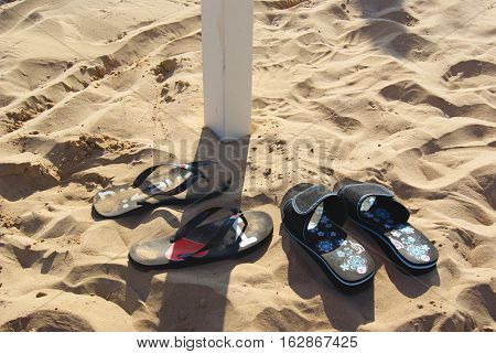 Two pairs of slippers flip-flops sprinkled sand beach. I love Venezia flip-flops. One slippers in pole shadow. lots of traces around.