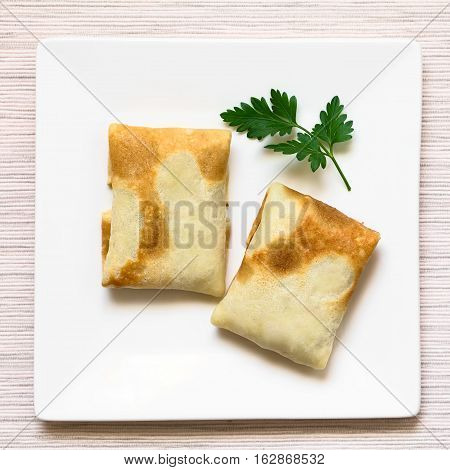 Folded crepes stuffed with a savory meat filling on plate garnished with parsley photographed overhead with natural light