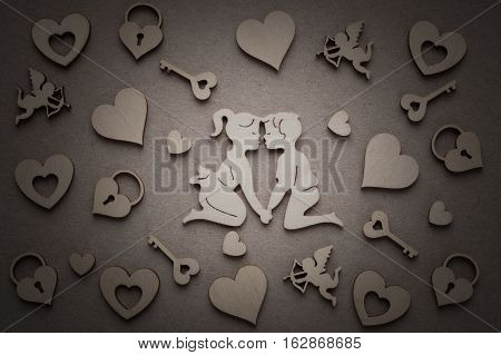 Wooden Silhouettes Of Men And Women Are Inclined To Each Other For Kiss On Paper Background With Wooden Silhouettes Of Hearts Amurs Castles Keys. Vignette.