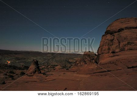 Nighttime desert landscape with stars and tail lights