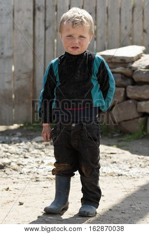STINKA UKRAINE - APRIL 14 2016 - funny little pig boy dressed stands in a yard in rubber boots on April 14 2016 in Stinka village.