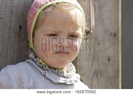 STINKA UKRAINE - APRIL 14 2016 - grimaced little girl closeup with rush on her cheeks stands at the wicket on April 14 2016 in Stinka village.