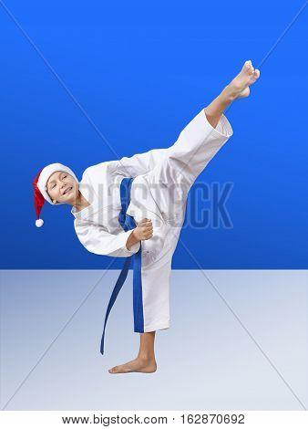 In cap of Santa Claus sportsman beats roundhouse kick