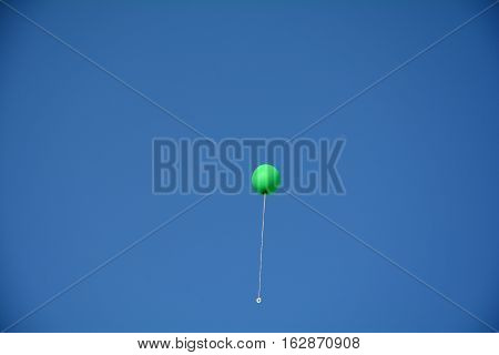 Green balloon with string high flies in the blue sky