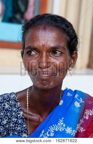 KERALA, INDIA. 23 January 2011:  Rural residents in daily life. Closeup portrait of a dark-skinned Indian woman waiting on the shore of the husband-fisherman...   Chowara, Kerala, South-west India.