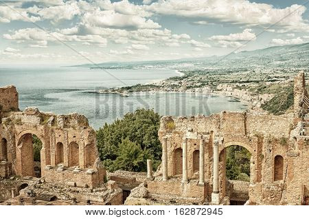 The ancient roman-greek amphitheater with the Giardini Naxos bay in the back in Taormina Sicily Italy (HDR image with black and gold filter)