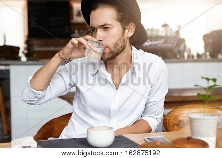 Young Caucasian Hipster Dressed In White Shirt Drinking Water Out Of Glass During Coffee Break At Ca
