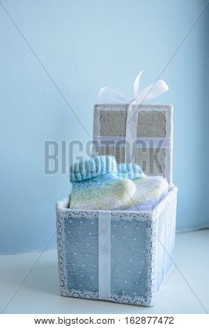 cute knit booties in festive gift box with lace and satin ribbon on the birth of baby boy