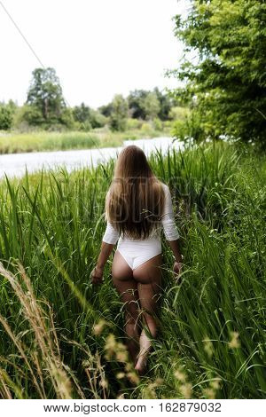 Blond Caucasian Woman Standing Outdoors In Green Grass Wearing White Leotards From Back