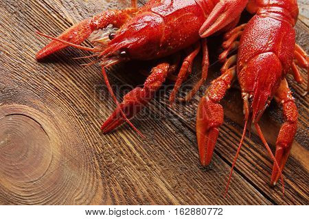 two boiled red crawfish on wooden surface.