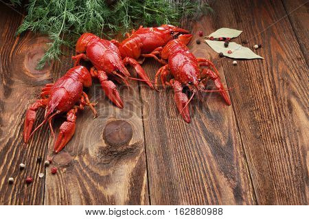 boiled crawfish on wooden surface with dill