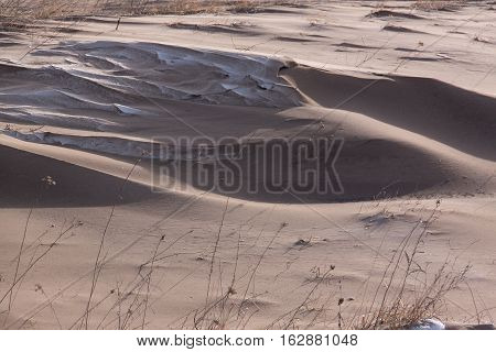 Very dirty snow as result of strong wind. Wind erosion of fertile land. Aeolian processes. Ukraine Kyiv region.