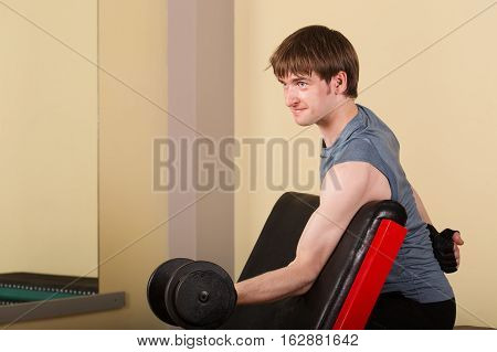 Man doing exercise for biceps with hand weights. Working with free weights. Healthy lifestyle concept. Fitness.