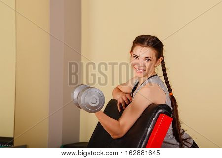 Cute girl doing exercise for biceps with dumbbells. Working with free weights. Healthy lifestyle concept. Fitness.