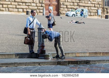 Businessmen Drinking Water At A Drinking Fountain At The Palazzo Pitti In Florence, Italy