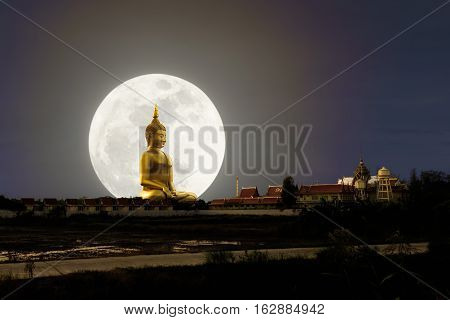 Big Buddha image at Wat Muang Ang Thong province Thailand with supper full moon in background multiple exposure technique