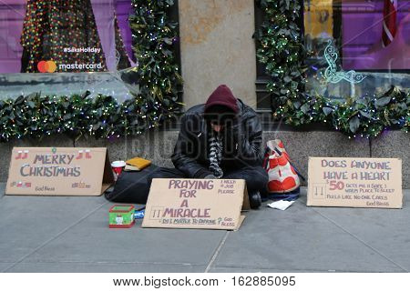 NEW YORK - DECEMBER 15, 2016: Homeless man in front of Sacks Fifth Avenue store in Midtown Manhattan