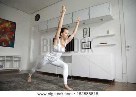 Sporty beautiful young woman practicing yoga, standing in Warrior one exercise, Virabhadrasana 1 pose, working out, wearing sportswear, indoor full length, home interior background