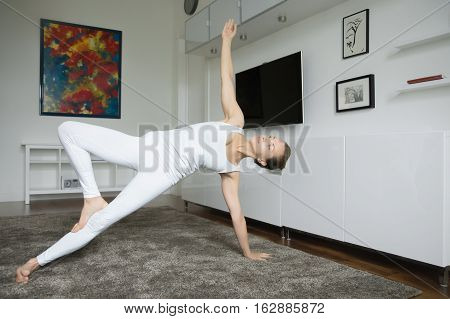Sporty attractive young woman practicing yoga, standing in Side Plank exercise, variation of Vasisthasana pose, working out, wearing white sportswear, indoor full length, home interior background