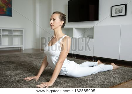 Sporty attractive young woman practicing yoga, stretching in Cobra exercise, Bhujangasana pose, working out, wearing white sportswear, indoor full length, home interior background