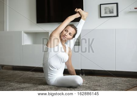 Portrait of sporty attractive young woman practicing yoga, sitting in Compass exercise, Surya Yantrasana pose, working out, wearing white sportswear, indoor full length, home interior background