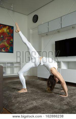 Attractive woman practicing yoga, standing in Bridge, One legged Wheel exercise, Eka Pada Urdhva Dhanurasana pose, working out, wearing white sportswear, indoor full length, home interior background