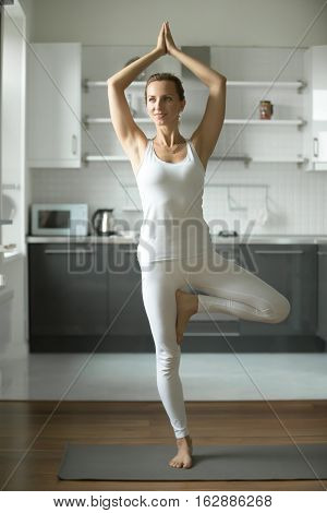 Happy smiling sporty attractive young woman practicing yoga, standing in Tree exercise, Vrksasana pose, working out, wearing white sportswear, indoor full length, home interior background