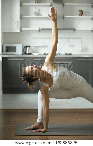 Beautiful Sporty young woman practicing yoga, standing in Extended Side Angle exercise, Utthita parsvakonasana pose, working out, wearing white sportswear, indoor, home interior background