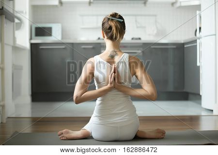 Sporty attractive woman practicing yoga, sitting in variation of Cow Face exercise, Gomukasana pose, working out, hands in namaste behind the back, indoor, home interior background. Rear view