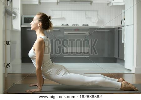 Sporty attractive young woman practicing yoga, standing in upward facing dog exercise, urdhva mukha shvanasana pose, working out, wearing white sportswear, indoor full length, home interior background