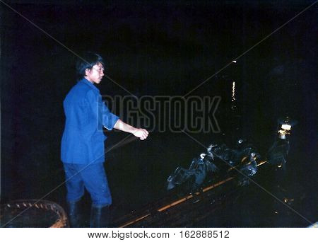 GUILIN / CHINA - CIRCA 1987: A fisherman fishes on the Li River during the night with trained great cormorants (Phalacrocorax carbo).