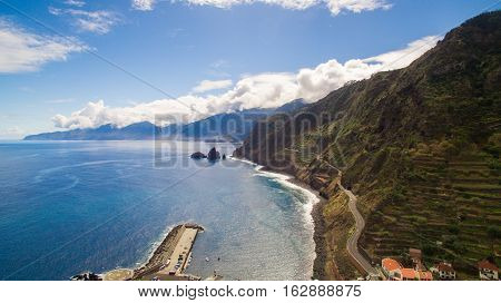 Coastal road with steep coast and beautiful blue ocean and sky, Madeira, Portugal