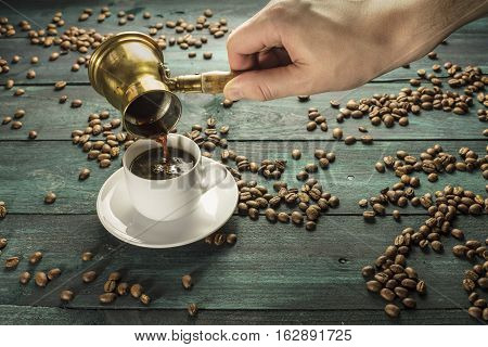 Strong coffee being poured from a vintage coffee pot into a white porcelain cup, on a dark background with scattered coffee beans