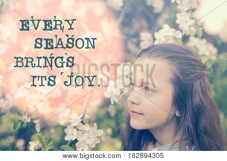 every season brings its joy proverb printed on image with child girl close to blossom apple tree