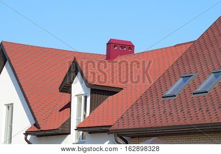 A house with a roof made of metal sheets. The house with gables windows and metal roof equipped with overflow and protection from snow.