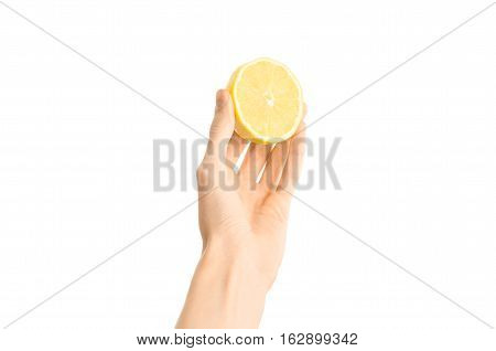 Healthy Eating And Diet Topic: Human Hand Holding Half Of Lemon Isolated On A White Background In Th