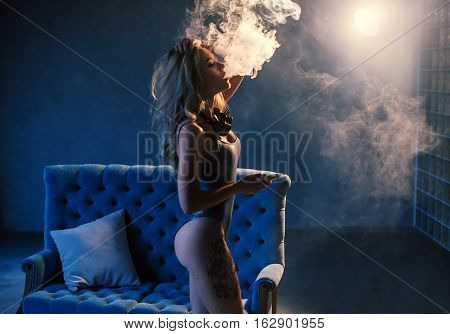Sexy Blonde In Lingerie Smokes Electronic Cigarette. The Model Vaping A Vaporizer In The Studio.
