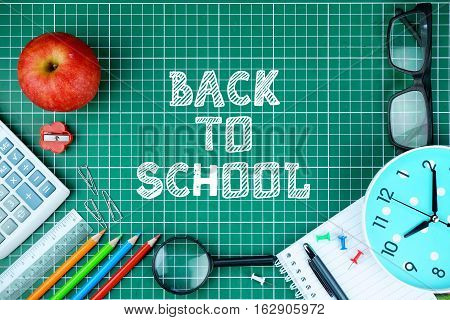 Top view of school supplies and BACK TO SCHOOL inscription written on cutting mat.