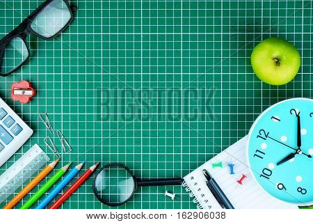 Back to school concept. School supplies on cutting mat background. Back to school concept with stationery. Schoolchild and student studies accessories. Top view.