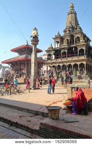 PATAN, NEPAL - DECEMBER 19, 2014: Garuda statue on column and Krishna Mandir temple at Durbar Square
