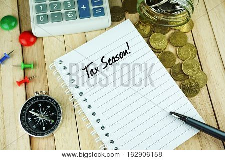 Overhead view of compass, pin, calculator, coins, pen and open notebook written with Tax Season on wooden background. Business Concept.