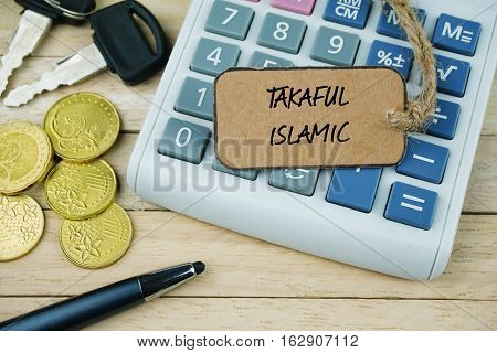Paper tag with TAKAFUL ISLAMIC word on calculator, Business conceptual.