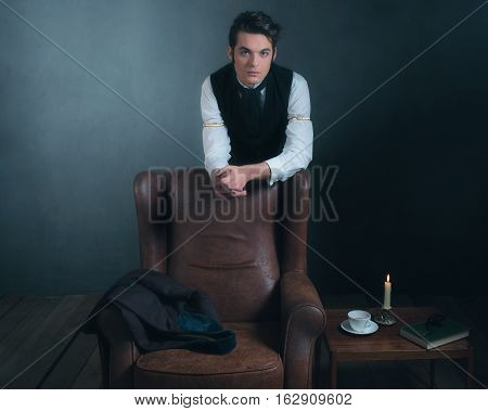Retro Victorian Man Leaning On Back Of Leather Chair In Living Room.