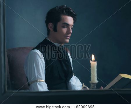 Retro Victorian Man Reading Book By Candlelight Sitting By Window.