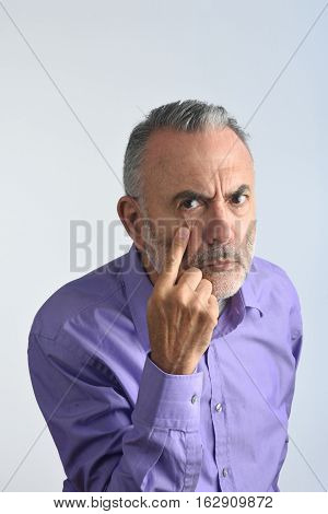 Man with gaze and finger in eye  with a white background