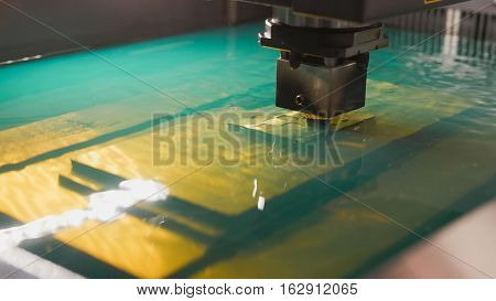 Automatic factory - cutting of sheet metal process in water, front view, close up