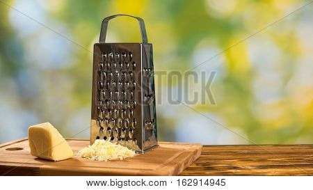 Grater and parmesan cheese on the wooden table on green background